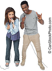 Portrait of a young couple singing into microphones over...