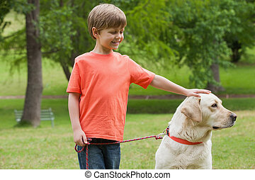 Happy boy with pet dog at park