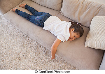 High angle view of a young girl sleeping on sofa in the...