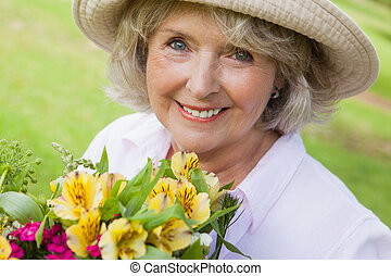 Close-up of smiling mature woman holding flowers at park -...