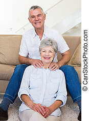Man giving his relaxed senior wife a shoulder rub smiling at camera at home in living room