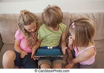 Three kids using digital tablet in