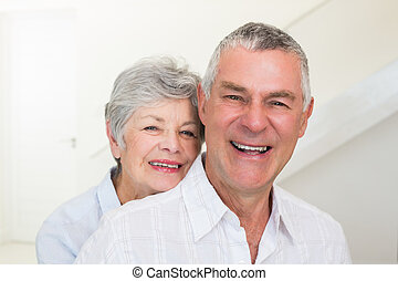 Retired couple smiling at camera at home in living room