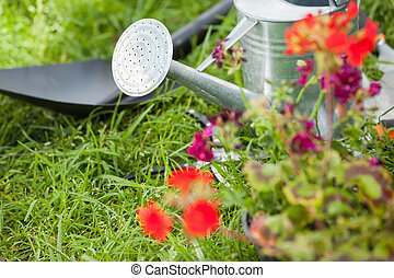 Spade and watering can by flowers at park