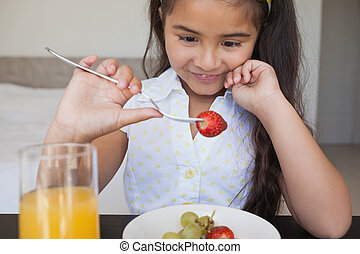 Close-up of a smiling girl eating fruits