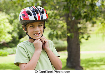 Smiling boy wearing bicycle helmet at park - Portrait of a...