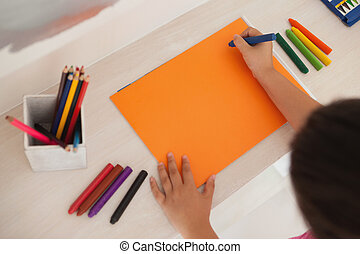 High angle of a girl drawing on orange paper at home