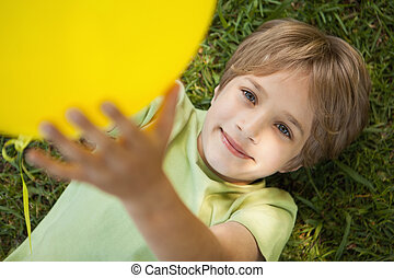 Young boy with yellow balloon at park - High angle view of a...