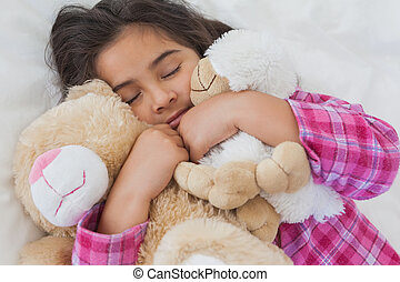 Girl sleeping with stuffed toys in - Close-up of a young...