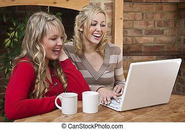 Computer and Coffee - Two beautiful young women at home...