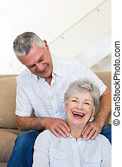 Man giving his senior wife a shoulder rub who is smiling at camera at home in living room