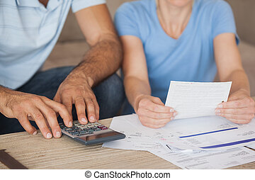 Mid section of a couple with bills and calculator - Close-up...