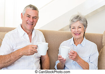 Senior couple sitting on couch drinking coffee smiling at...