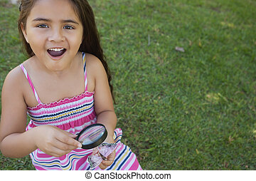 Girl examining a butterfly with magnifying glass at park -...