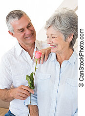 Senior man offering a rose to his partner at home in living...