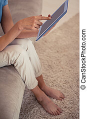 Low section of a young woman using digital tablet in the...