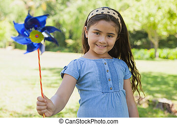 Cute little girl holding pinwheel at park - Portrait of cute...