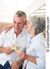 Senior couple sitting on couch having white wine