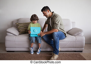 Father and son with gift box sitting in living room - Full...