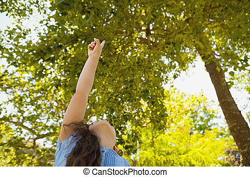Young girl pointing up at trees in park