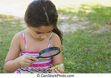 Girl examining a leaf with magnifying glass at park - Young...