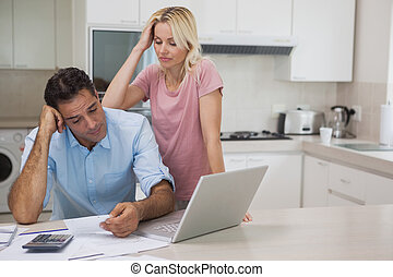 Unhappy couple with bills and laptop in kitchen - Unhappy...