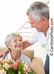 Senior man giving his partner a bouquet of flowers at home...