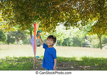 Happy young boy holding kite at par - Full length portrait...
