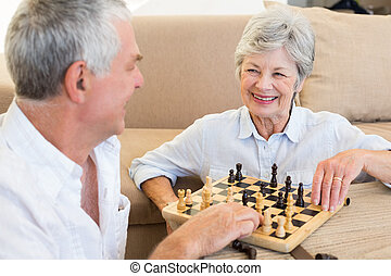 Senior couple sitting on floor playing chess at home in...
