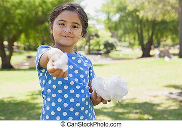 Beautiful little girl holding cotton candy at park