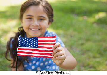 Young girl holding the American flag at park - Close-up...