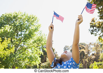 Girl holding up two American flags - Low angle view of a...