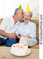 Senior couple sitting on couch celebrating a birthday at...