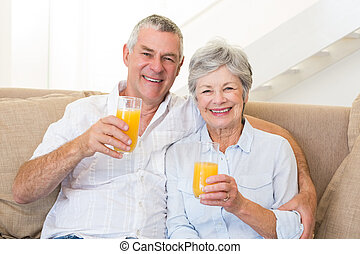 Senior couple sitting on couch drinking orange juice at home...