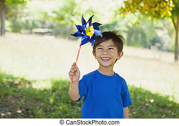Happy cute little boy holding pinwheel at park - Portrait of...