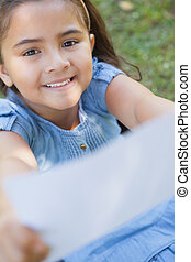 Smiling girl holding out a blurred paper at park