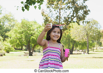 Cheerful girl blowing soap bubbles at park