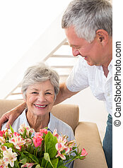 Senior man giving his partner a bouquet of flowers smiling...
