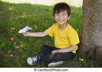 Happy boy playing with a paper plane at park - Portrait of a...
