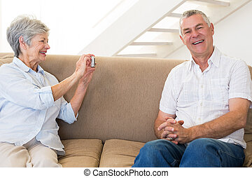 Retired woman taking photo of her partner on the couch at...