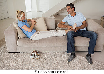 Full length of a relaxed couple sitting in living room -...