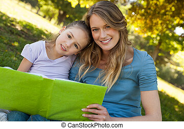 Happy mother and daughter reading a book at park - Portrait...