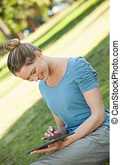 Relaxed woman using digital tablet at park