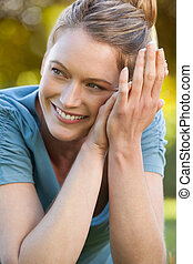 Close-up portrait of beautiful relaxed woman at park -...