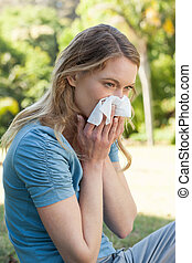 Woman blowing nose with tissue pape - Side view of a young...