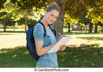 Beautiful young woman writing on clipboard at park - Side...