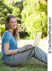 Relaxed woman using laptop at park