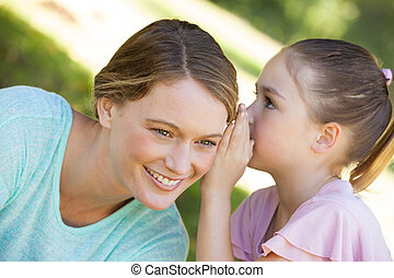 Girl whispering secret into mother's ear at park - Close-up...