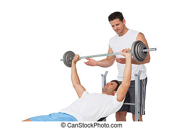 Trainer helping fit man to lift the barbell bench press -...
