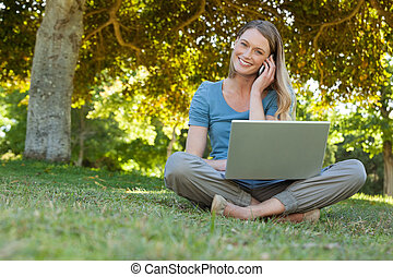 Relaxed woman using laptop and mobile phone at park